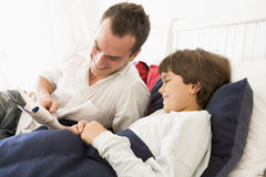 Man reading book to young boy in bed smiling Royalty Free Stock Images