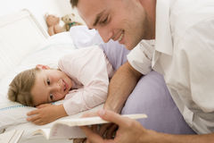 Man reading book to young girl in bed smiling Royalty Free Stock Photography