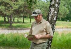 Man reading book under birch tree Stock Photos