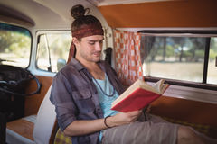 Man reading book in van Royalty Free Stock Images