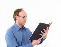 A man reading a book. A man wearing a blue shirt and spectacles,  reading a book Stock Images