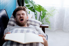 Man reading book with yawn sleep. Royalty Free Stock Images