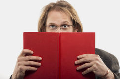Man reading book. Young blond handsome man wearing glasses is reading a red book. Shot in studio. Isolated Stock Images