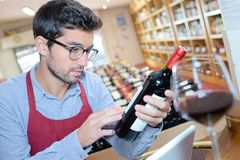 Man reading bottle wine label in wine shop Royalty Free Stock Image