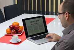 Man reading breaking news on a laptop Royalty Free Stock Photo