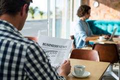 Man reading a business newspaper in coffee shop Stock Photo