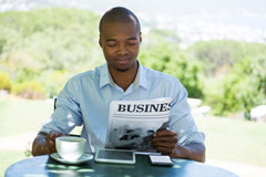 Man reading business newspaper at restaurant. Young man reading business newspaper at restaurant Stock Image