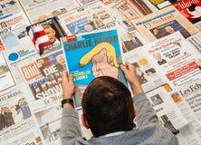 Man reading Charlie Hebdo magazine. PARIS, FRANCE - JAN 21, 2017: Man holding Charlie Hebdo with Trump caricature above major international newspaper journalism Stock Photography