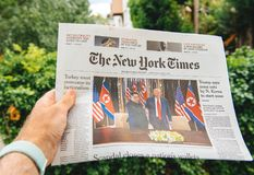 Man reading in city newapsper Kim-Trump meeting. PARIS, FRANCE - JUNE 13, 2018: Man reading The New York Times newspaper showing on cover U.S. President Donald stock photos