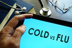 Man reading about cold vs flu. Man reading about cold vs flu on a tablet Royalty Free Stock Photo