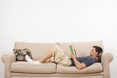 Man Reading on Couch stock photos