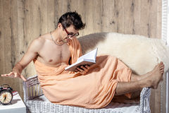 Man reading on couch when alarm clock rings Royalty Free Stock Image