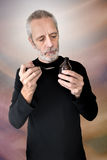 Man Reading Cough Syrup Label. A mature man is reading the label of a cough syrup bottle before to cure his sore throat and bronchitis Royalty Free Stock Image