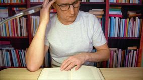 Man reading at the desk with lamp. Front view, thoughtful man in glasses reading book, while sitting at the desk with lamp in front of bookshelves in the stock video