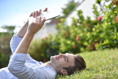 Man reading digital e-book on tablet lying in grass Stock Photography