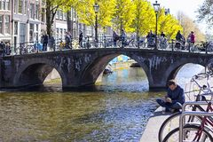 Man Reading and Drinking Coffee in Front of One of The Canals in Amsterdam Royalty Free Stock Photography