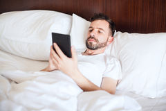 Man reading an e-book in bed Royalty Free Stock Photography