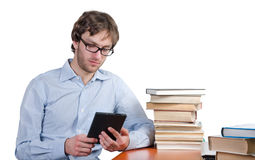 Man reading an e-book. Man at a table with books read e-books Royalty Free Stock Photography