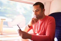 Man Reading E Book On Train Royalty Free Stock Photos