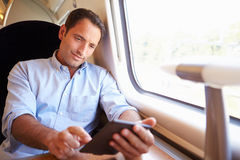 Man Reading E Book On Train Stock Photography