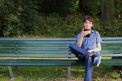 A man reading an e-reader on a bench Stock Images