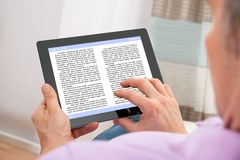 Man reading ebook. Close-up Of A Man Reading Ebook On Digital Tablet Stock Photography