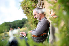 Man reading ebook from garden Stock Images