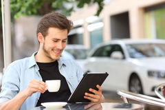 Man reading an ebook or tablet in a coffee shop. Happy man reading an ebook or tablet in a coffee shop terrace holding a cup of tea