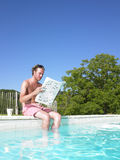 Man Reading at Edge of Swimming Pool Stock Photo