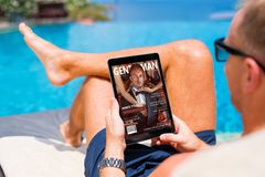 Man reading emagazine on vacation by the pool stock photos