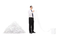Man reading file in front of pile of shredded paper. Isolated on white background Stock Photography