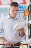 Man reading food labels. Man doing grocery shopping at the supermarket and reading a food label on a box, shopping and nutrition concept Stock Photo
