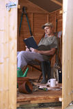 Man reading in garden shed. Man reading book while sitting in deckchair in his garden shed stock photos