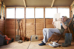 Man reading in garden shed. Man checking share prices while sitting in deckchair in his garden shed stock photography