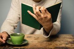 Man is reading and having coffee Royalty Free Stock Photography
