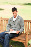 Man reading his book on the bench Stock Photos