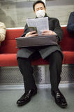 Man reading his newspapper in the Tokyo metro Royalty Free Stock Photos