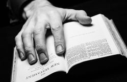 A man reading the Holy Bible. With one hand Stock Photo