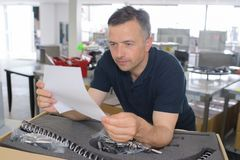 Man reading instruction for 3d printer on tablet computer royalty free stock photography