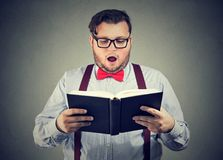 Man reading interesting book with shocked face expression Stock Photo