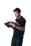 Man reading from a large book Stock Photo