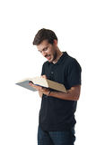 Man reading from a large book and smiling Stock Images