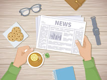 Man reading the latest news at breakfast. Human hands holding tea with lemon and newspaper. A good start of the day before working. View from above Stock Photo