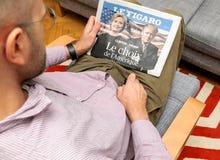 Man reading Le Figaro magazine Hillary Clinton and Donald Trump Royalty Free Stock Image