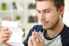 Man reading a leaflet before to take a pill Stock Image