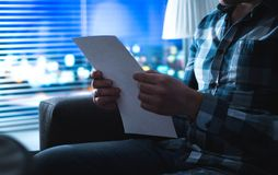 Man reading letter in dark at night. Person writing note in shadows home by the window. Sudden inspiration or bad news. Foreclosure, insurance or mortgage Royalty Free Stock Photo
