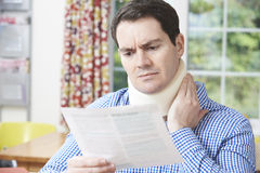 Man Reading Letter After Receiving Neck Injury Stock Images