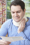 Man Reading Letter After Receiving Neck Injury Stock Photography