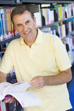 Man reading in library. Man reading book in a library Stock Photo