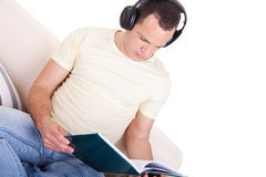 Man reading and listening music with headphones on Royalty Free Stock Photo